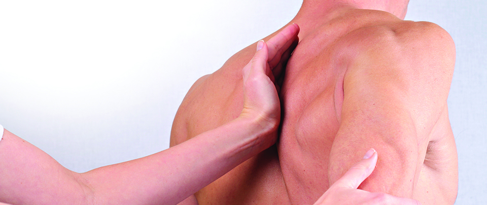image of a mans back with a massage therapists hand applied to the shoulderblade